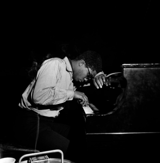 Black-and-white photo of Herbie Hancock in profile, he plays the piano with one hand, his other hand and his forehead lean on the piano