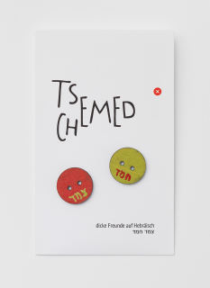 Piece of white paper with German and Hebrew text with two wooden yellow and red buttons