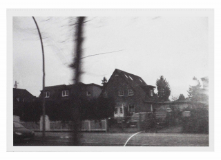 Black and white photograph of a house, the foreground is blurred as if the photographer was moving while the picture was being taken