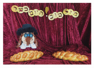 Golden paper Hebrew letters, a mannequin with binoculars, and two challah bread loafs are composed on red velvet fabric