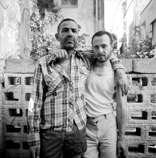 Black and white portrait photo of two men with beards standing in front a cinderblock wall with their arms around each other