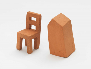 Miniature clay sculptures of a chair and a tombstone shaped figure