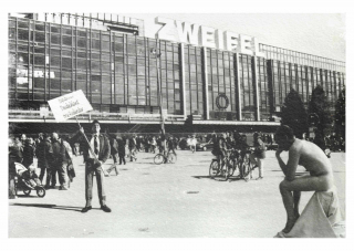 A historical black and white photograph of a crowd outside a large building. On the right there is a naked man sitting on cloth, on the left there is a man holding a picket sign