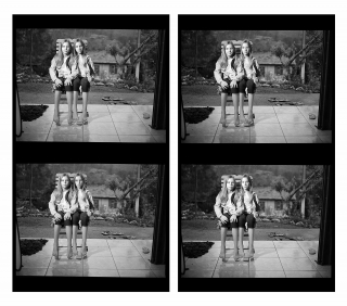 A four pannel repeated black and white scene of two young girls wearing identical outfits sitting next to each other on the same wooden chair