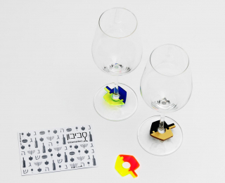 Two wineglasses with colorful dreidel-shaped charms around their stems