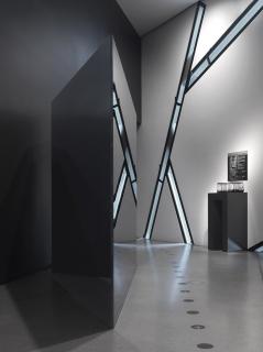 Dunkle, eckige Skulptur in einem leeren Raum mit schmalem Fensterband, das sich in der Oberfläche der Skulptur spiegelt