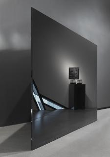 Die Spiegelung zeigt eine Wandbeschilderung und einen Ständer mit Kopfhörern