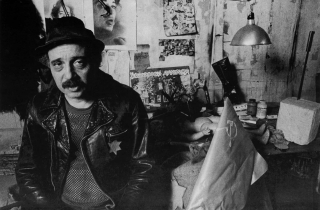 Black and white photograph of Boris Lurie in his studio, the walls and desk are filled with pictures and projects, Lurie wears a leather jacket with the star of david