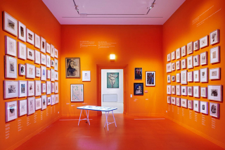 Exhibit space, the bright orange walls are covered in paintings and drawings by Boris Lurie