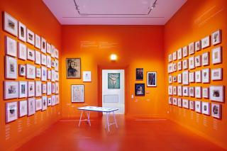 Ausstellungsraum mit orangen Wänden, an denen viele gerahmte Zeichnungen und Ölbilder hängen