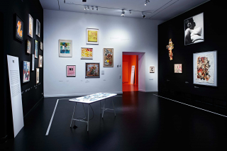 Exhibit space, the black and white walls are covered with colorful paintings, drawings, and collages
