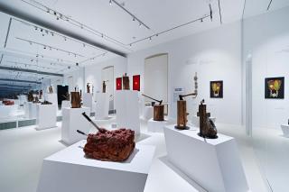 Skulpturen, z.B Äxte in Holzklötzen auf weißen Säulen, spiegeln sich in einem großflächigen Wandspiegel