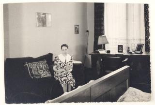 Schwarz-Weiß-Fotografie: eine Frau sitzt auf einem Sofa, in den den Händen ein Buch haltend