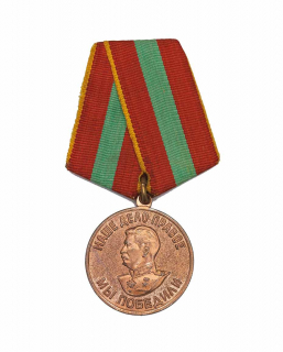 Bronzefarbene Medaille mit einem Reliefbild Stalins und kyrillischer Schrift an einem rot-grün gestreiften Band