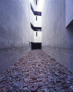 Installazione di Menashe Kadishman: numerose piastre di ferro, nelle quali sono ritagliati dei volti, si trovano sul fondo di un vuoto