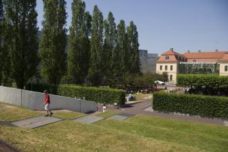 Jardín con forma de terraza en primer plano, al fondo a la derecha el edificio antiguo con el patio acristalado.