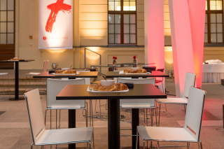 Chairs and tables set in the glass courtyard of the Jewish Museum Berlinr