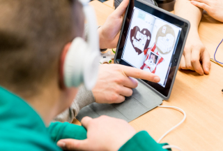 Ein Hand wischt über das iPad während ein Schüler mit Kopfhörern auf das Display sieht.