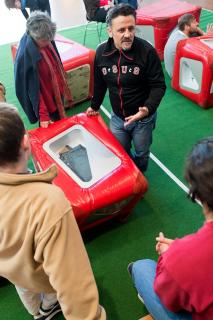 Ein Museumsguide zeigt Jugendlichen einen Ausstellungswürfel