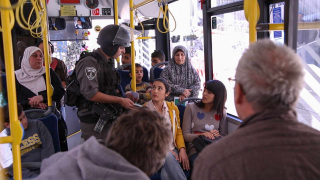 Bewaffneter Soldat kontrolliert die Ausweise von Zivilist*innen in einem Bus
