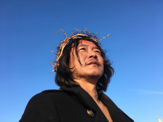Portrait photo of a man with a crown of thorns, taken from below, before a bright blue sky