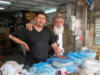 An older man puts his arm around a younger man, they pose behind a stand with flatbreads.