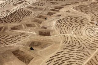 View from above of a desert landscape with patterns from ploughed or planted areas
