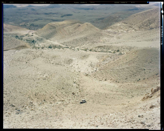 View from above on hilly desert landscape with single car