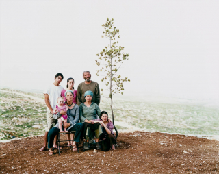 Seven people of different ages, including a toddler, posing as a family photo outdoors next to a young tree in front of an otherwise bare landscape