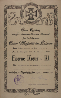 Urkunde, umrahmt mit Lorbeermotiv, oben zentral Darstellung eines Eisernen Kreuzes mit Jahreszahl 1914 und Krone