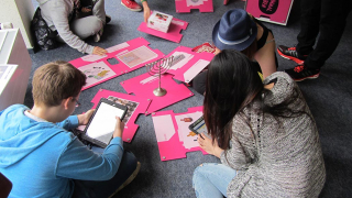 Schüler*innen sitzen auf dem Boden bei einem Workshop