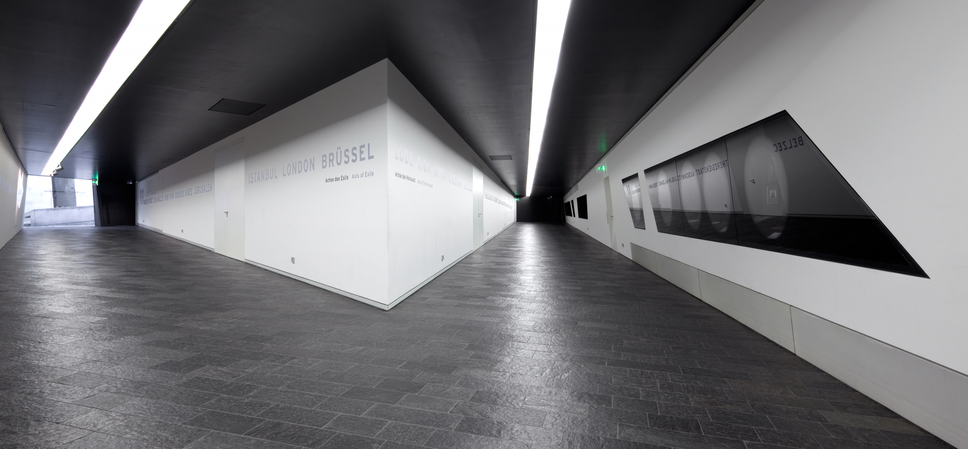 Fotografie: Blick in zwei Achsen, in den Wänden eingelassene Vitrinen und Städtenamen