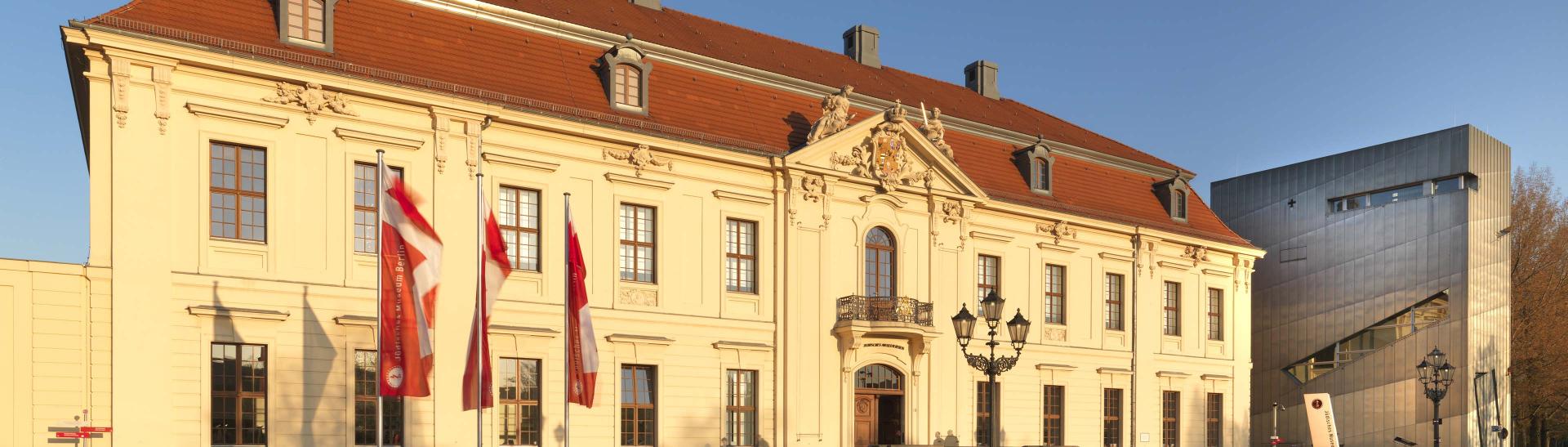 Altbau des Jüdischen Museums Berlin in der Abendsonne, mit drei Fahnen