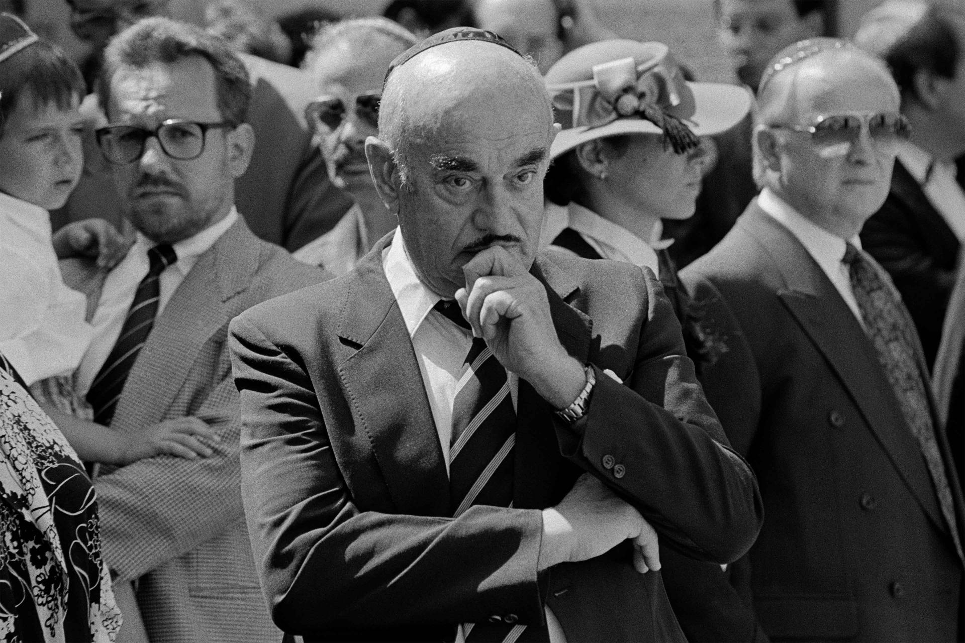 Schwarz-Weiß-Fotografie: Artur Brauner steht inmitten anderer Trauergäste, er hält die linke Hand an sein Kinn und winkelt den rechten Arm an.