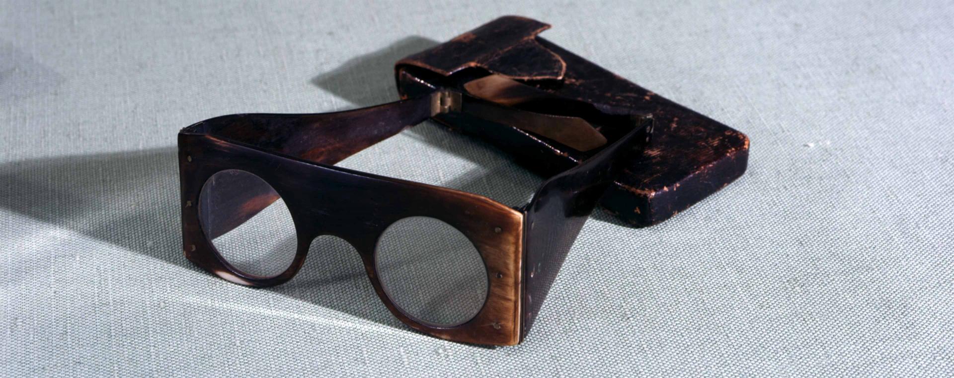 Quadratische Brille mit runden Gläsern, daneben ein passendes Etui