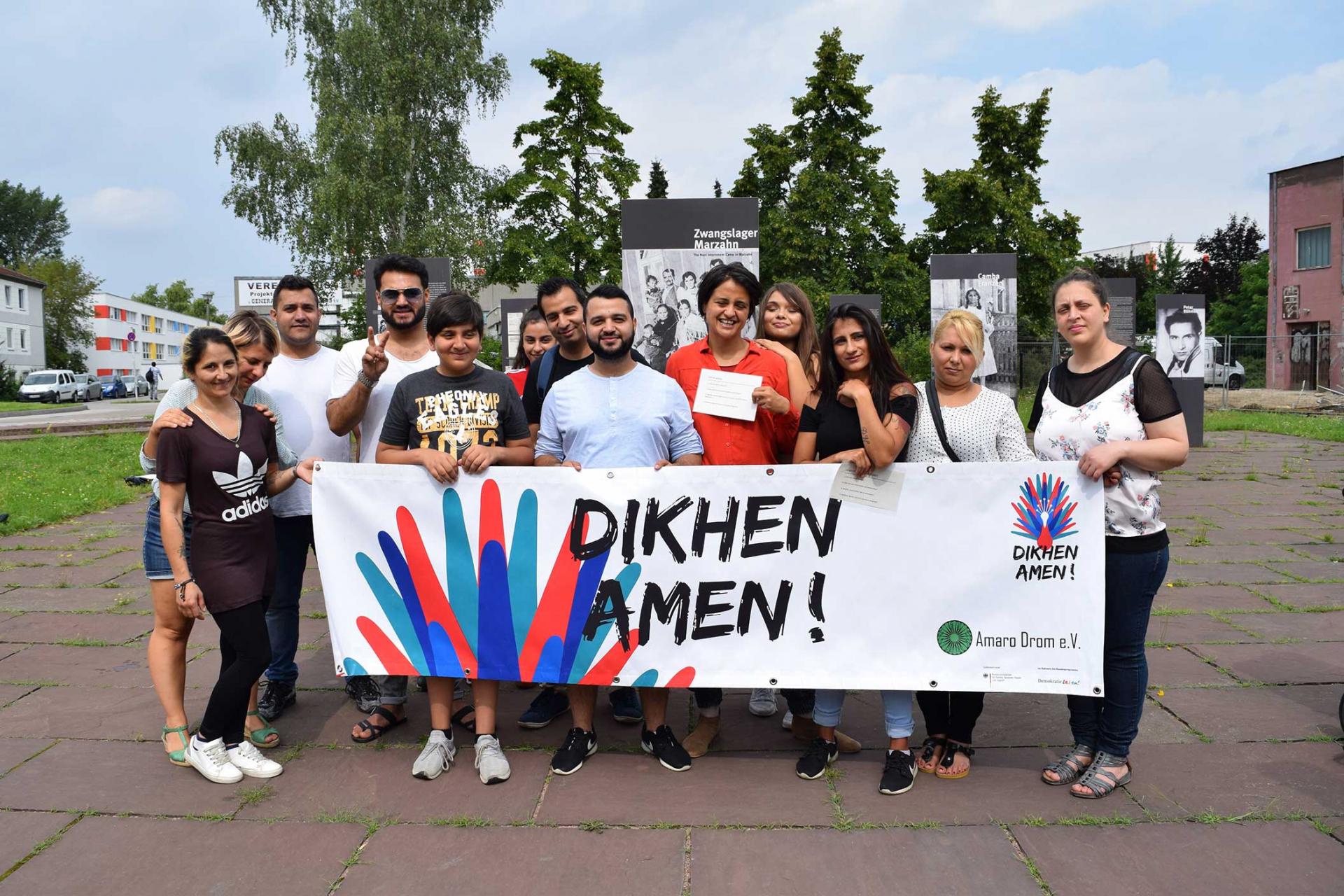 """Eine Gruppe Menschen, die ein Transparent mit der Aufschrift """"Dikhen Amen!"""" hält."""