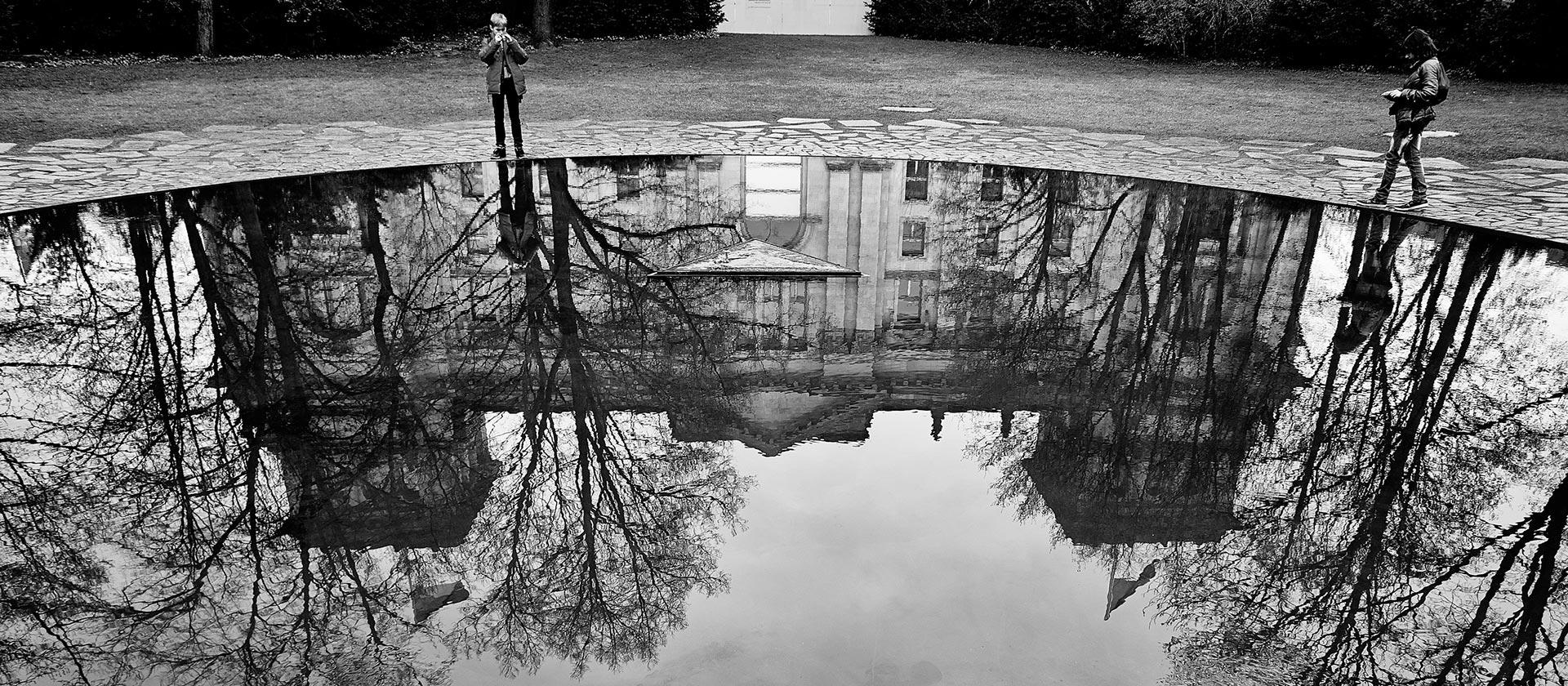 Ein Gebäude spiegelt sich im Wasser, schwarz-weiß Foto