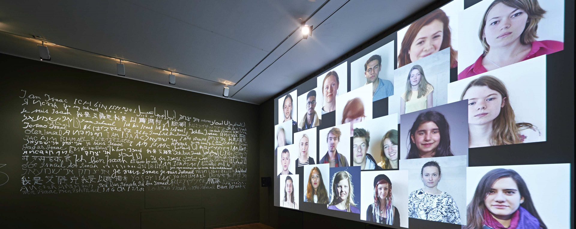 A wall reading »I am Isaak/Ismail« in several languages to the right and projected images of young peoples' faces to the lefte left