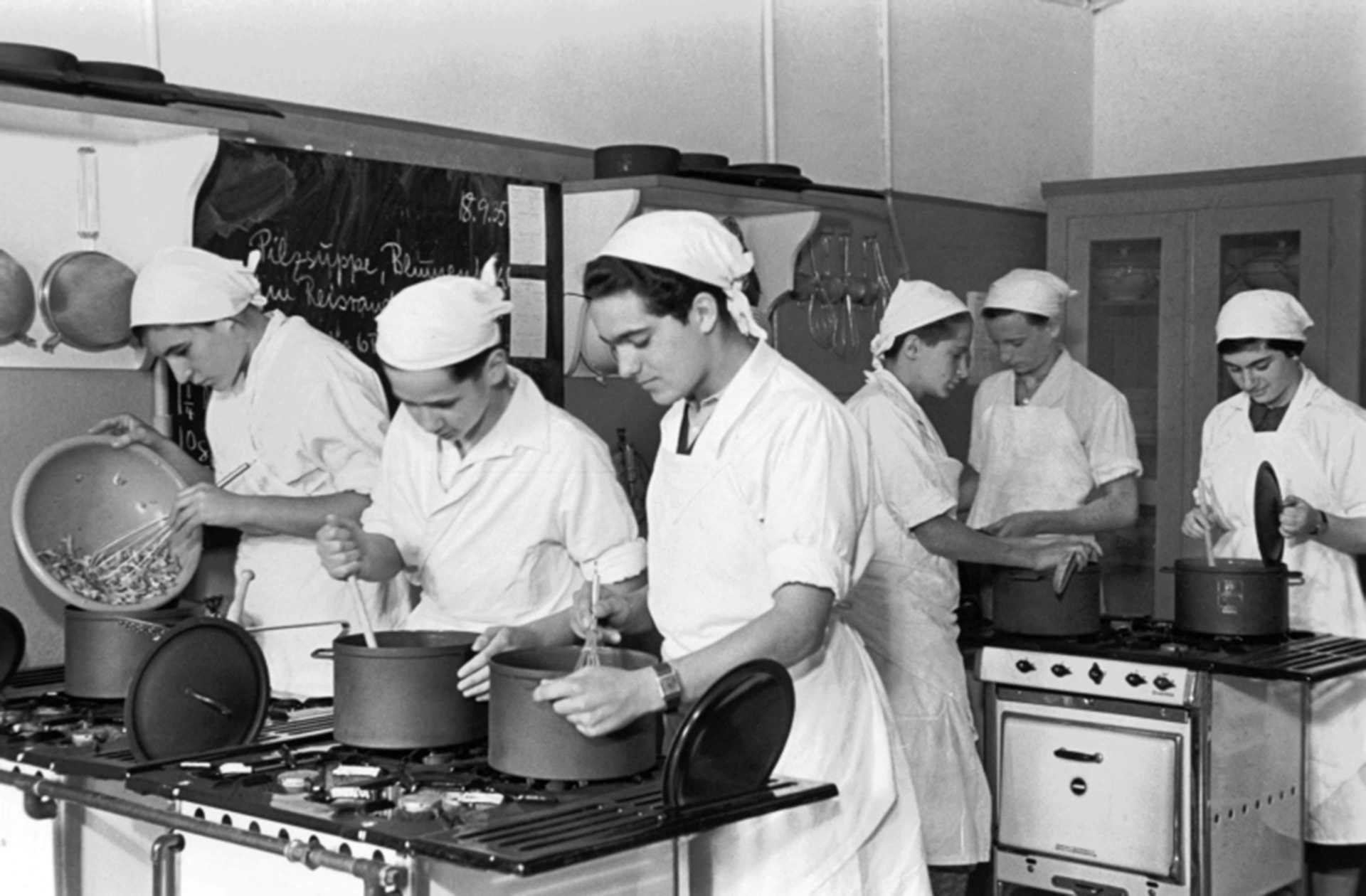 Black and white historical photograph of six students in a kitchen of the Theodor Herzl School, the students are wearing white aprons and white headscarves working hard at the stove cooking in pots