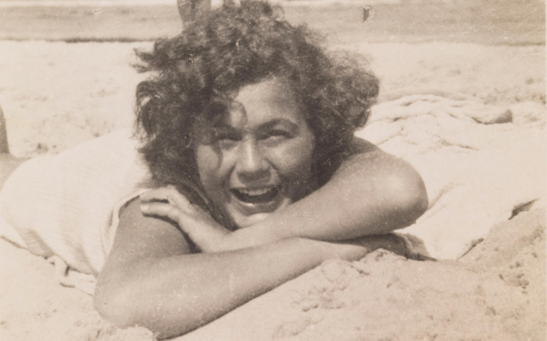 Black and white photo of a curly woman on the beach lying on her belly in the sand with a foot stretched out into the sky.