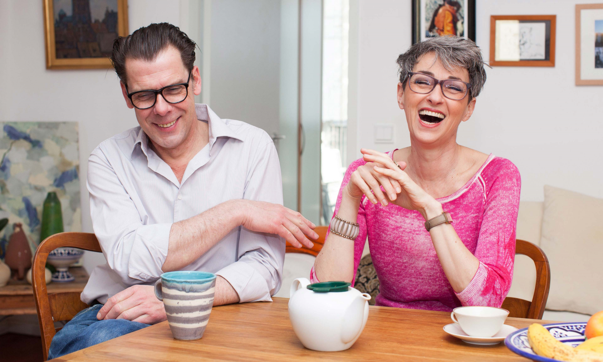 Man and woman laughing and sitting around a table