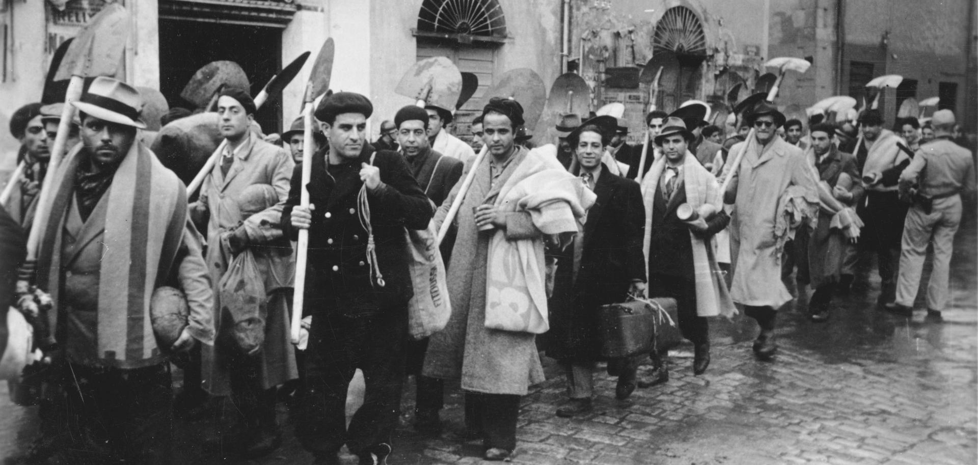 Eine Gruppe von Männern mit Gepäck und Spaten in der Hand