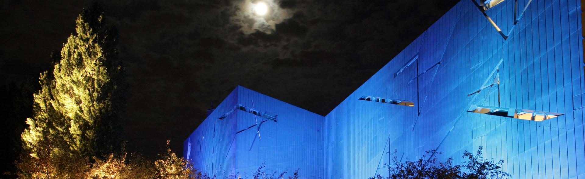 Libeskind-Bau blau angestrahlt, nachts, bei Vollmond