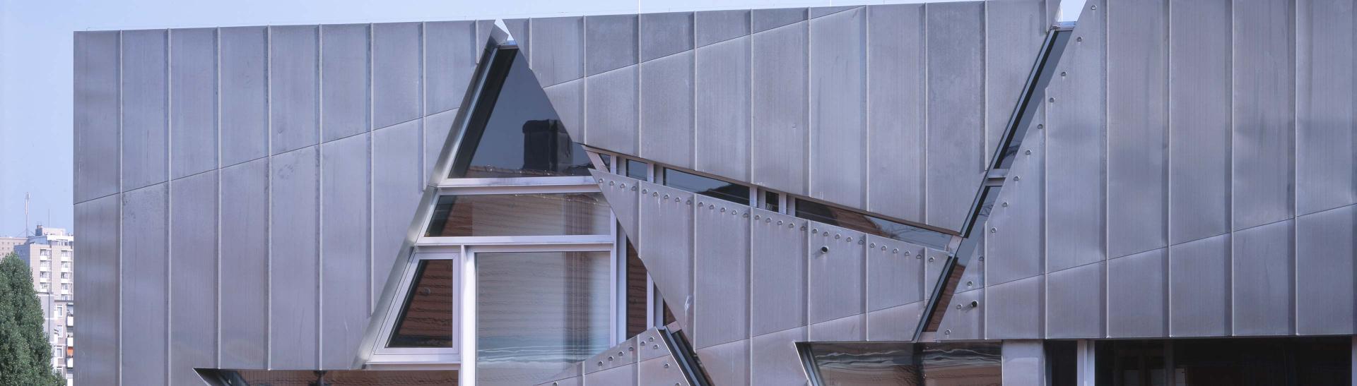 Teil der Fassade des Libeskind-Baus aus grauem Titanzink, mit einem dreieckigen Fenster