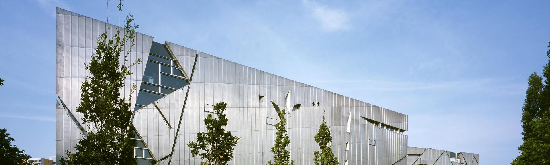 Teil des Libeskind-Baus mit vier Bäumen im Vordergrund
