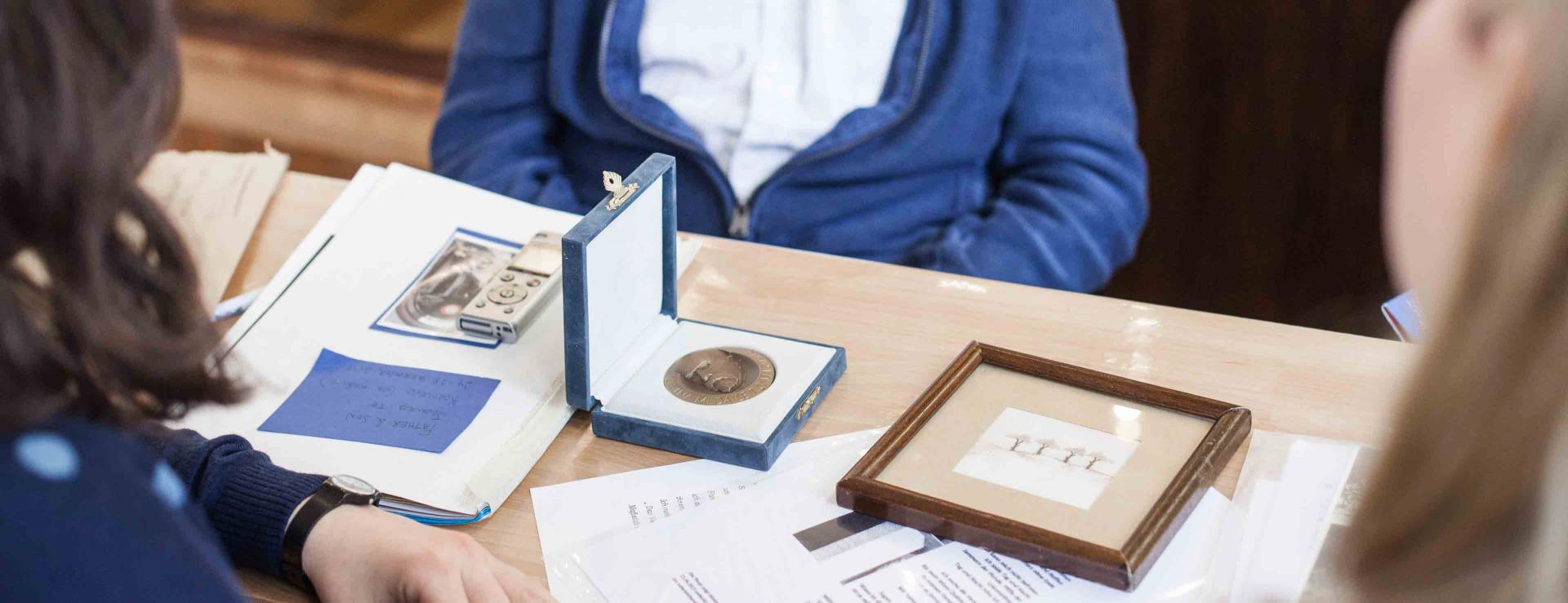 Mehrere Menschen sitzen um einen Tisch, auf dem Erinnerungsstücke und ein Aufnahmegerät liegen