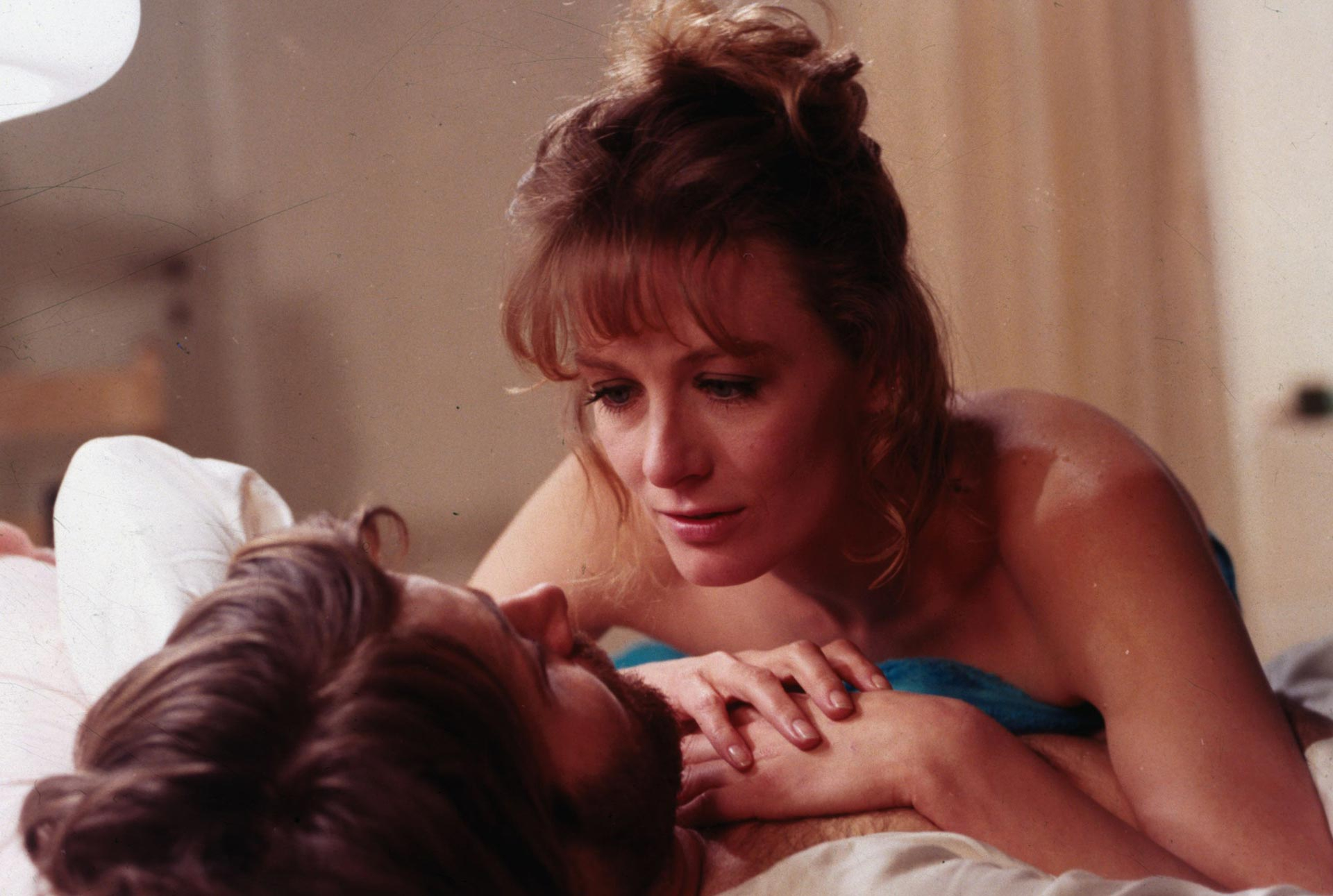 Film still of a woman laying on top of a man, they are looking at each other face to face