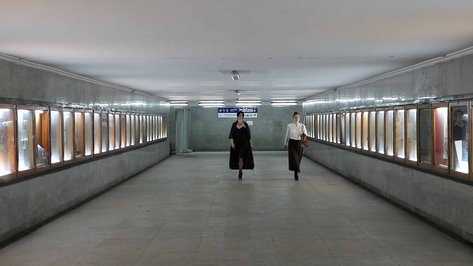 Two woman, one holding a violin and bow, walk towards the camera in an empty concrete hallway