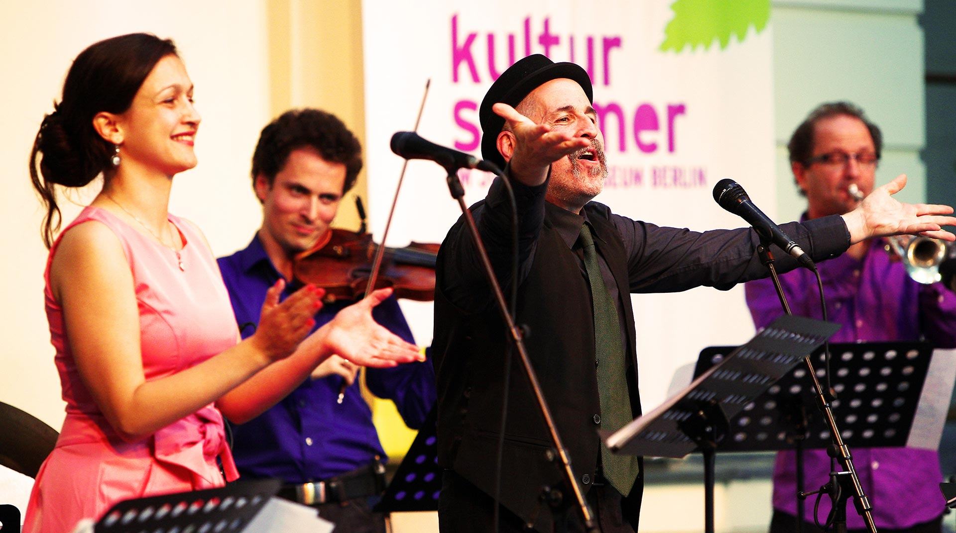 A group is performing music, one man is singing, one woman is clapping, and two other men are playing the violin and the trumpet