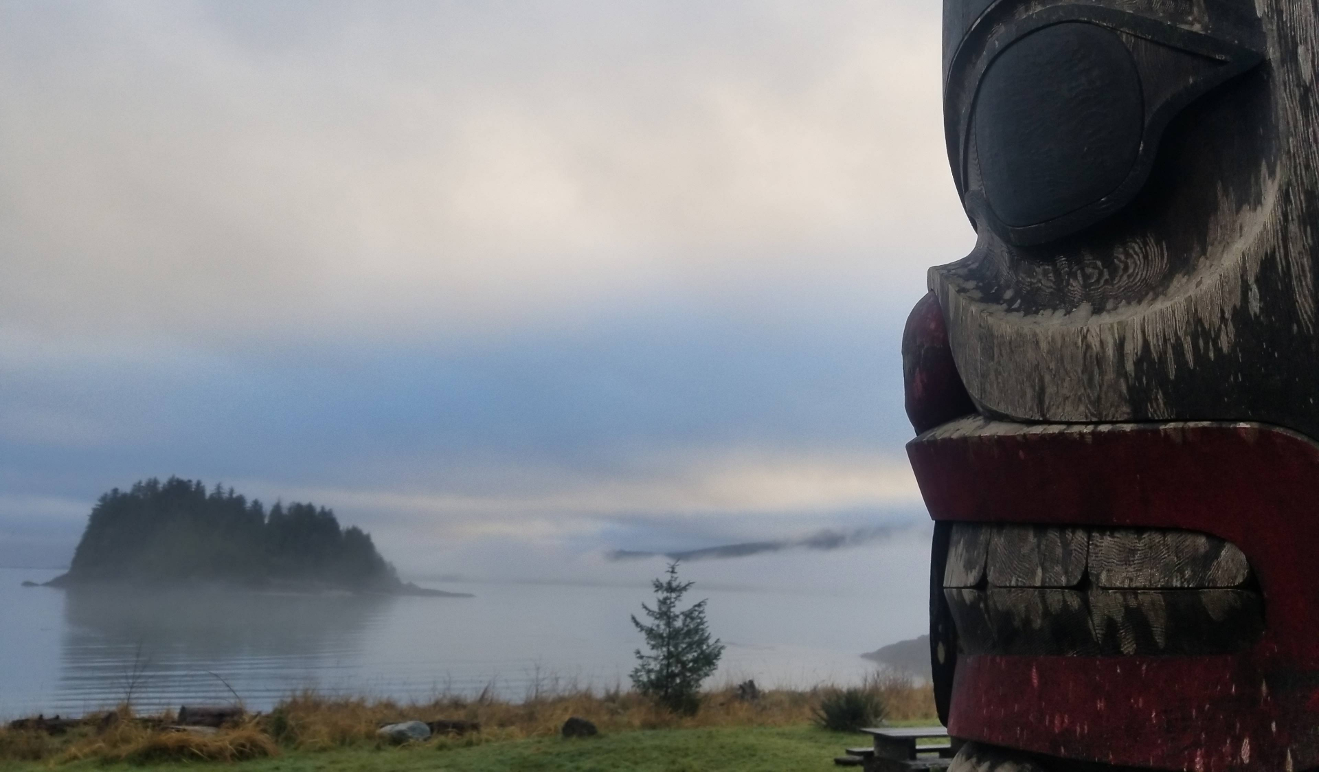 Photography of a totem pole in a foggy landscape with lake